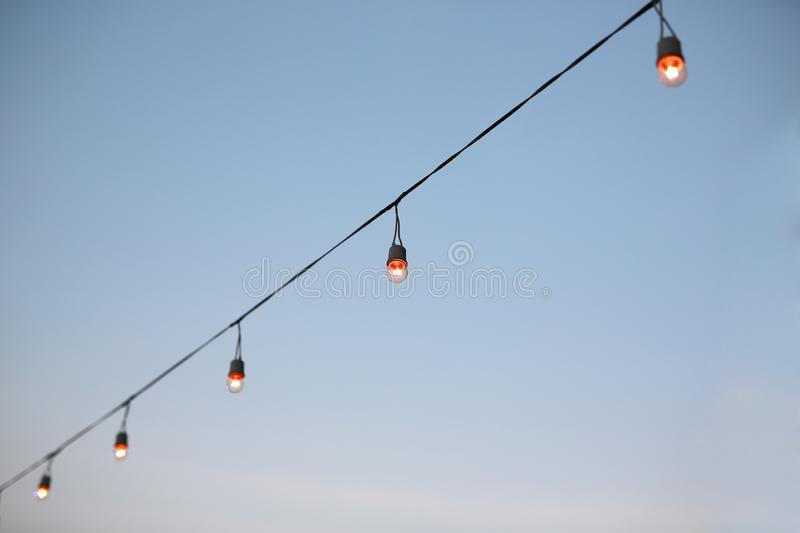 Row of light bulbs turned on over evening sky background.  royalty free stock photos