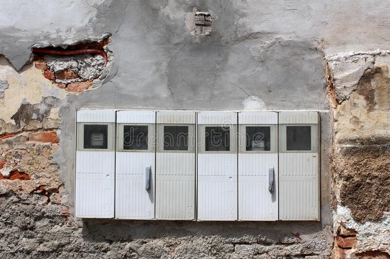 Row of locked closed new electrical meter boxes with safety switches visible through small glass mounted on old wall royalty free stock image