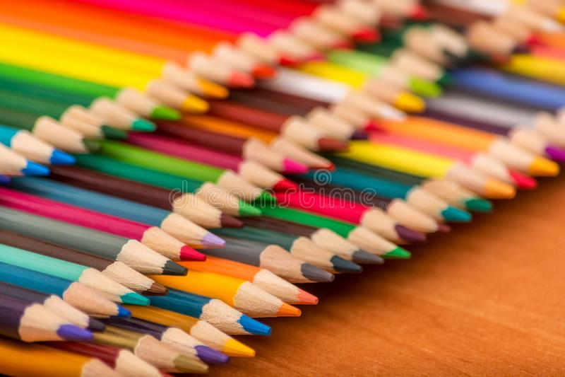 Row of many multicolored pencils on a wooden table background. Different colored pencils with space for text. Back to school.  royalty free stock photos