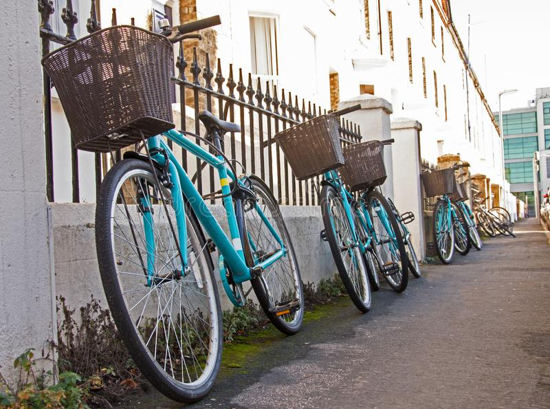 Row of matching rental student bicycles with baskets. A row of matching rental bicycles with baskets are chained up to a fence oute a student house in Cambridge royalty free stock images