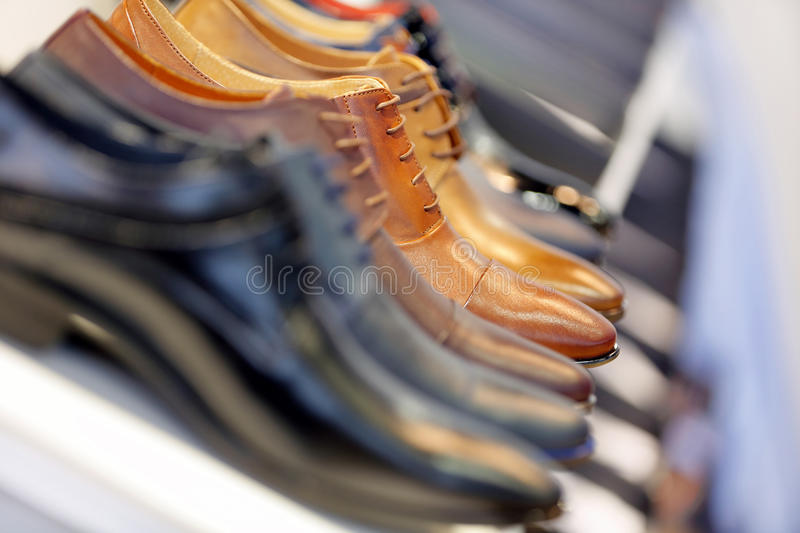 Row of men`s shoes in wardrobe or store royalty free stock images