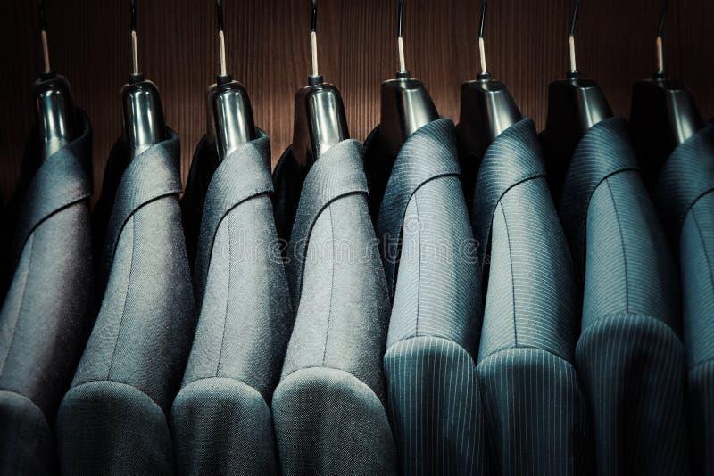 Row of men suit jackets on hangers. In store stock image