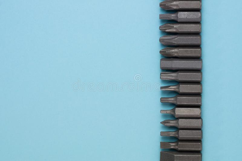 Row of metal bits for screwdriver in form of triangle on blue background. With copy space royalty free stock photo