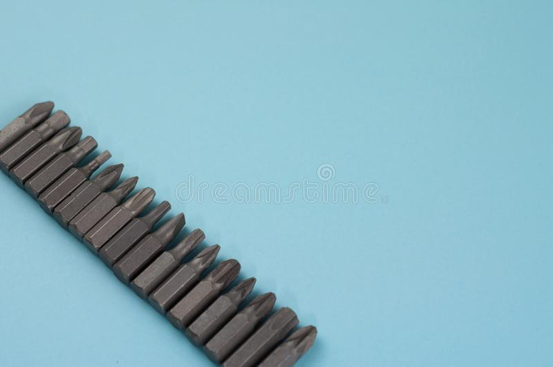 Row of metal bits for screwdriver in form of triangle on blue background. With copy space stock photo