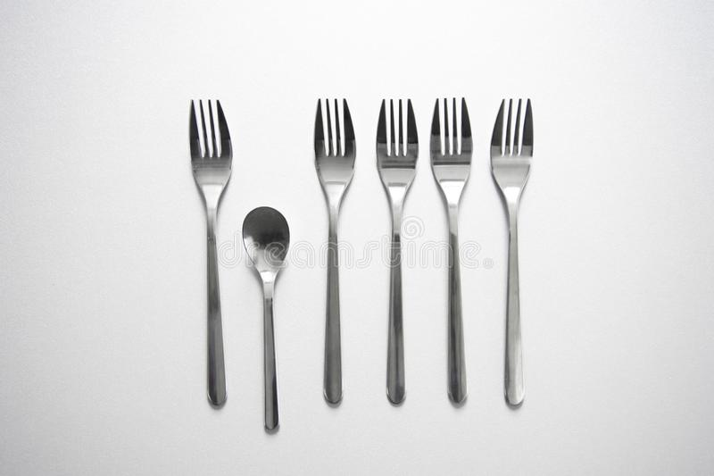 Row of metal fork with unique small spoon on grey background com stock photography