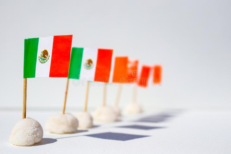 Row of mini Mexican flags in a row with interesting shadows - shallow depth of field with front one in sharp focu against white ba. A Row of mini Mexican flags stock photography