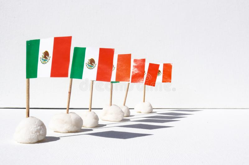 A row of mini Mexican flags with shadows on a white canvas background. A row of mini Mexican flags with shadows standing on a white canvas background stock photography