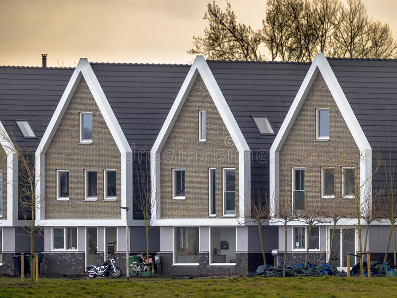 Row of modern houses at sunset. Row of modern identical free standing houses in the Netherlands at sunset stock image