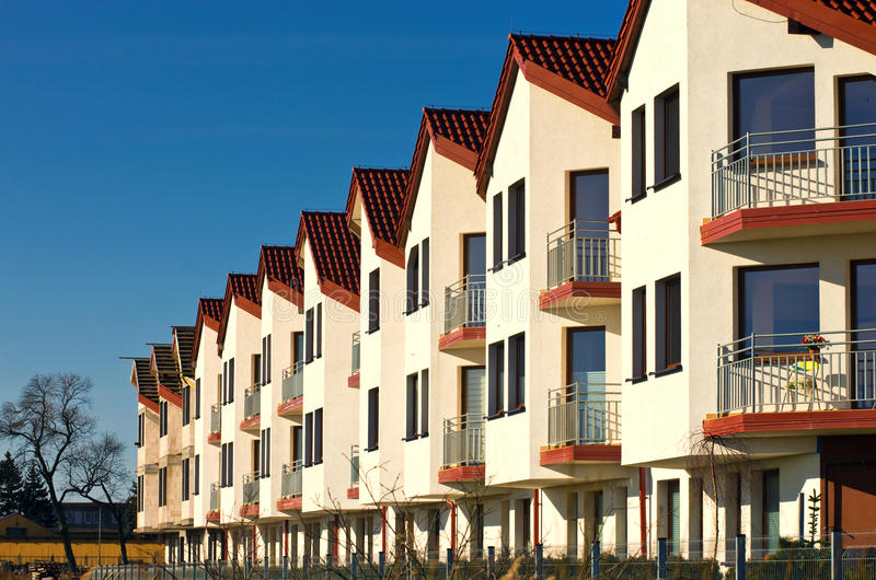 Row of modern houses. Row of modern white houses with balconies, blue sky background stock image