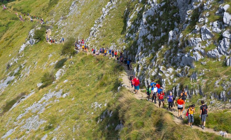 Row of mountaineers ascending the road to the top of Mount Ernio, Euskadi royalty free stock image
