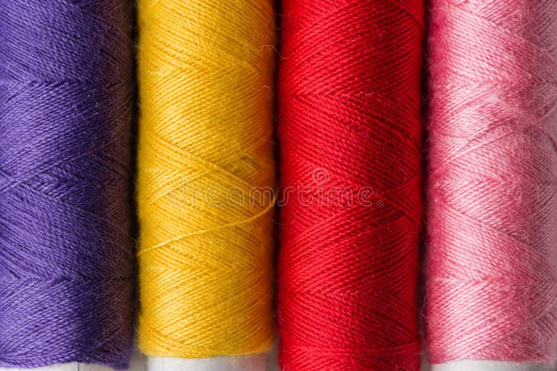 Row of multicolored rainbow palette sewing threads on cardboard spools. Crafts hobbies local artisan business interior decoration stock image