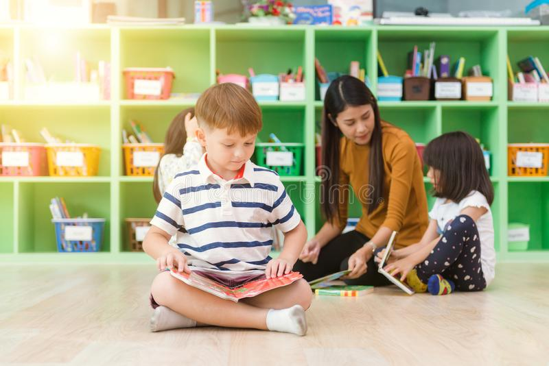 Row of multiethnic elementary students reading book in classroom. Vintage effect style pictures stock image