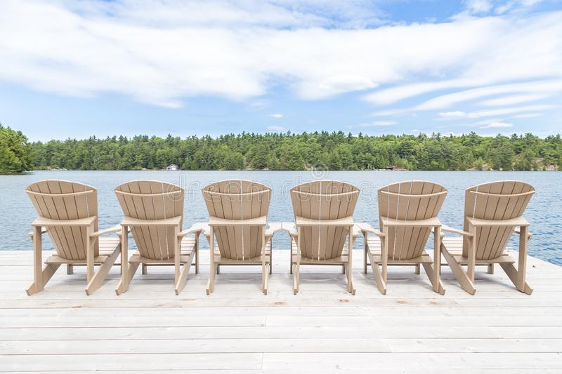 Row of Muskoka chairs on a dock looking onto the lake. stock photo