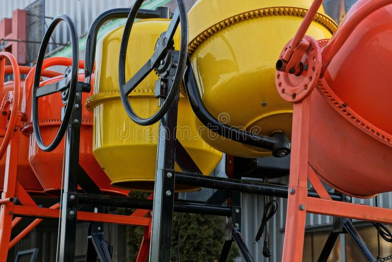 Row of new iron red and yellow concrete mixers royalty free stock photos