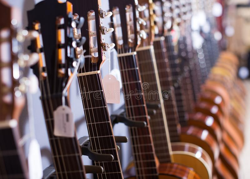 Row of new acoustic guitars in music shop. Row of new nec of acoustic guitars in music shop stock photography