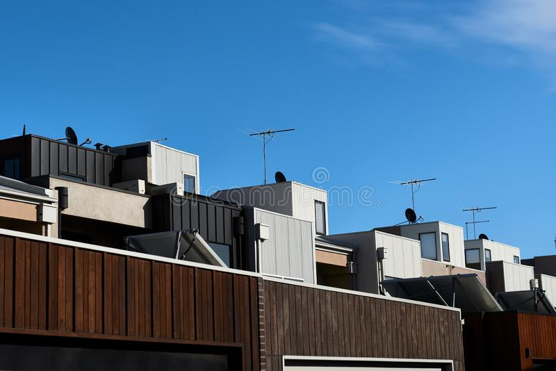 Architectural details showing a row of modern town house apartments on a sunny day and a blue sky. stock photos
