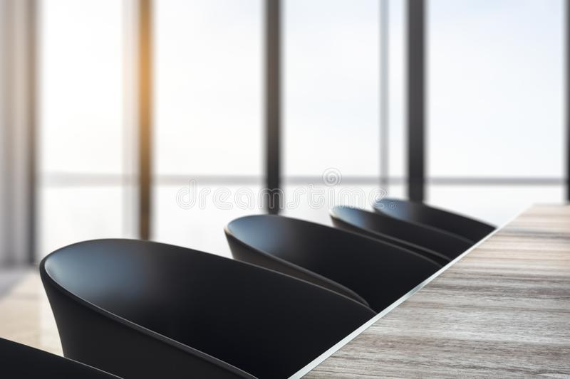 Row of office chairs. And wooden desktop in modern meeting room interior. Blurry window background. Side view. 3D Rendering royalty free illustration