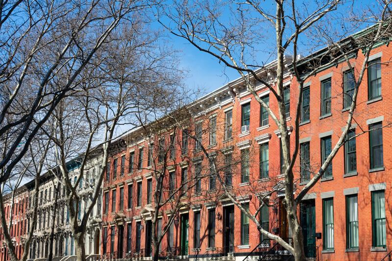 A Row of Old Colorful Brick Residential Buildings in Long Island City Queens New York. A row of old colorful brick residential townhouses with bare trees in Long stock images