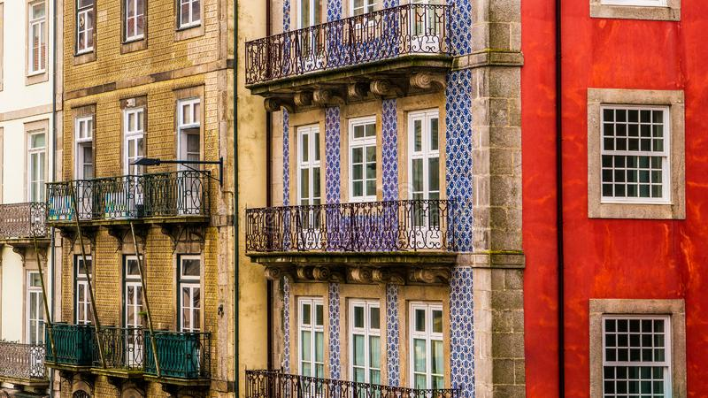 Row of old, colorful buildings with ornate balconies and tiles line a street in Porto, Portugal. Historic buildings in Porto, Portugal covered in colorful tiles stock images