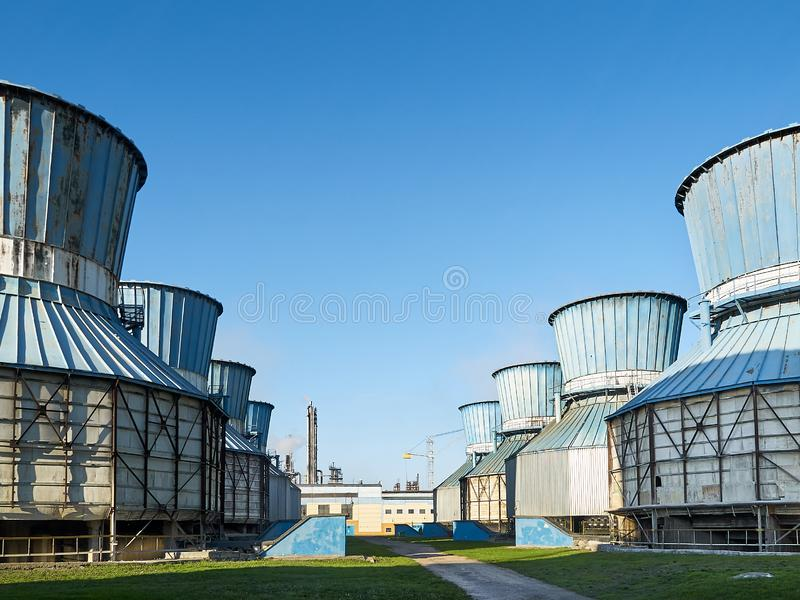 Row of old fan cooling towers for cooling circulating water of c. Hemical plant under clear blue sky royalty free stock photos
