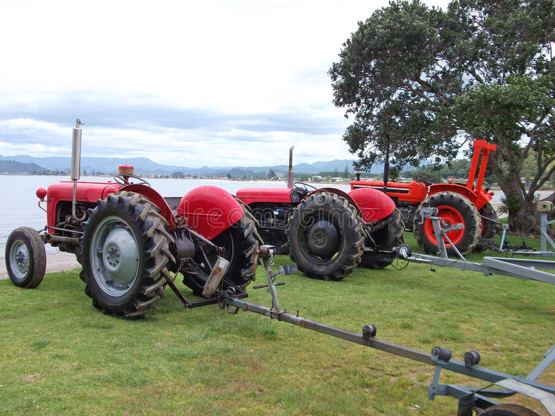 Row of old red tractors. A row of old red tractors on a beach, ready for recovering fishing boats from the sea. Photographed at Whitianga, Coromandel Peninsula stock images