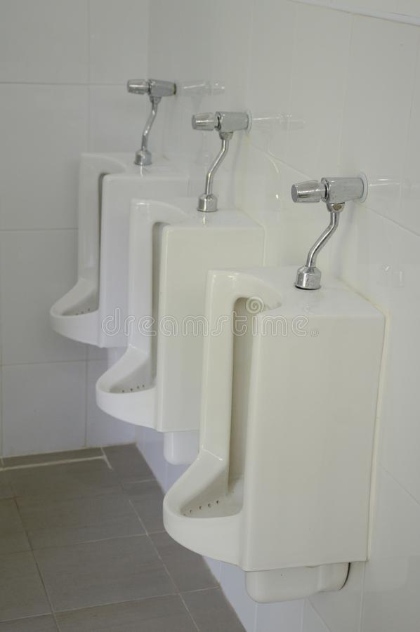 Row of old white urinals stock photo