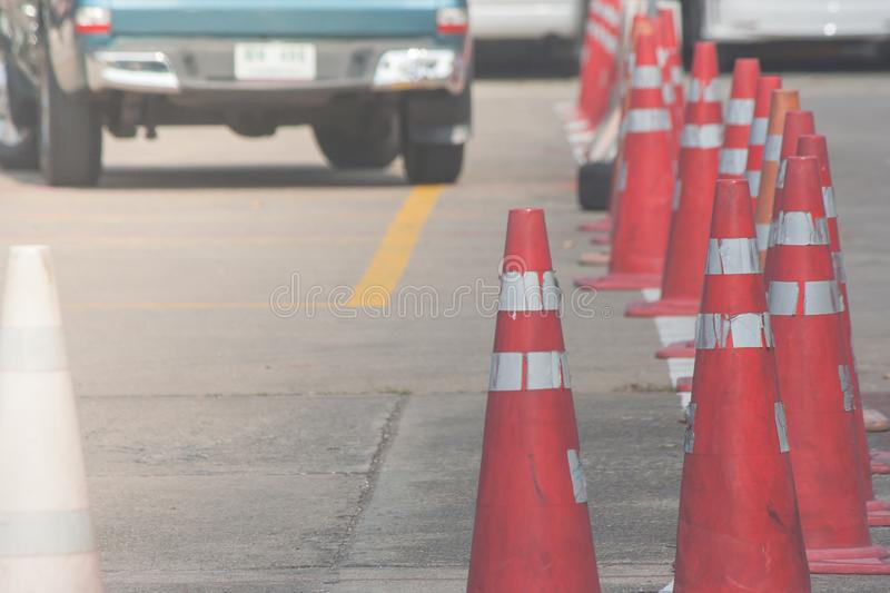 Row of orange traffic cones setting on roadway beside parking lot. royalty free stock photo