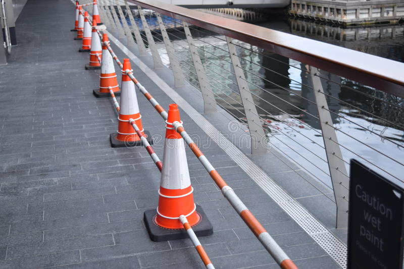 Row of orange and white cones on a bridge royalty free stock images