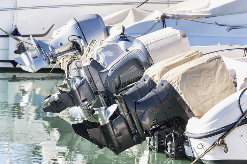A row of outboard nautical engines mounted on fiberglass boats.  stock images