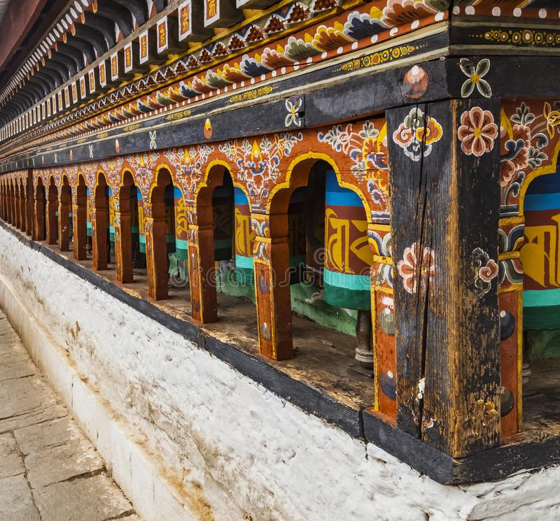 Row of painted turning prayer wheels mantra in Bhutan with traditional writing mantra which sounds as Om mani padme hum, literally royalty free stock images