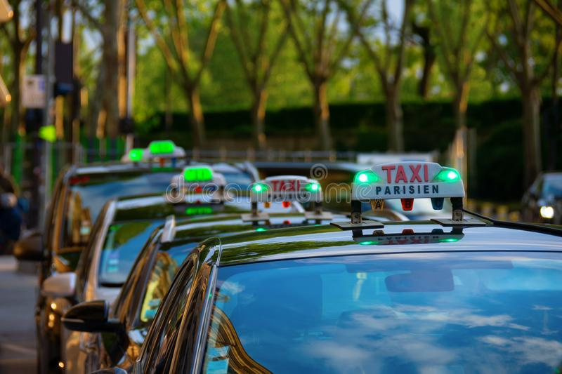 Row of Parisien taxis in the Republique District of Paris France. Row of Parisien taxis in the Republique District of Paris, France, with the lush green trees of stock photos