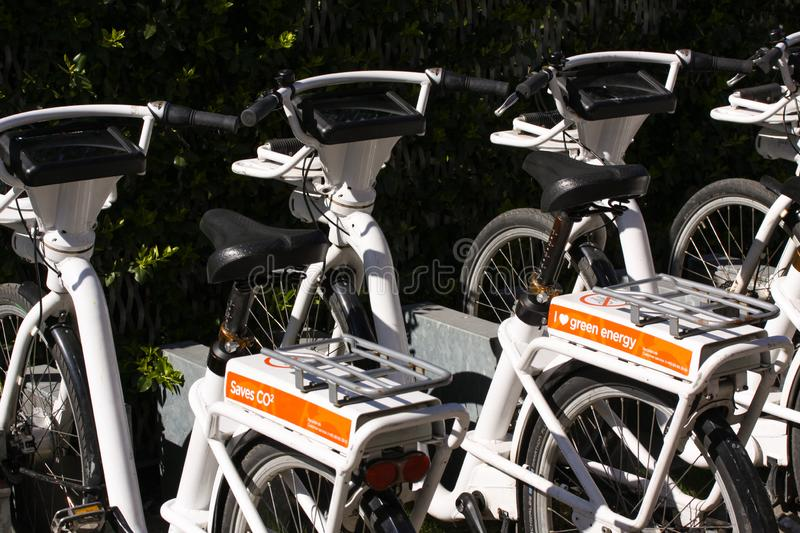 Row of parked city bikes for rent with bumper stickers saying Save CO2 and Green energy. royalty free stock image