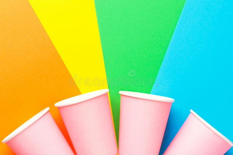 Row of pink paper drinking cups on multicolored pinwheel background. Funky retro style. Birthday party fest celebration kids fun royalty free stock photos