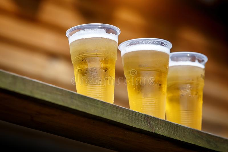 A row of plastic beer glasses with a beer on a party. stock image