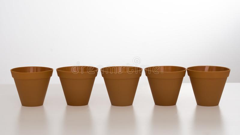 Row of plastic flower pots on white background with reflection. royalty free stock photos