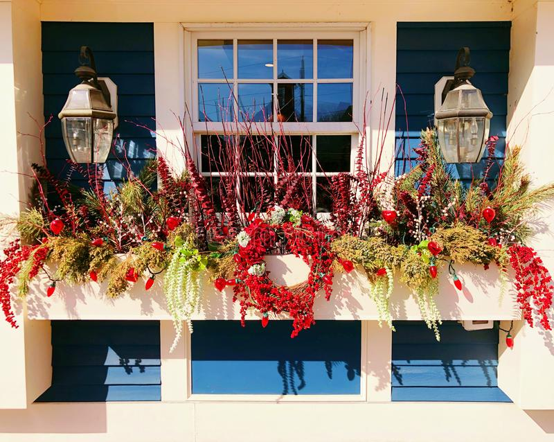 A row of potted artificial flowers hung on the window. Of s store in Kennebunk downtown street York County, Maine Maine United States stock photos