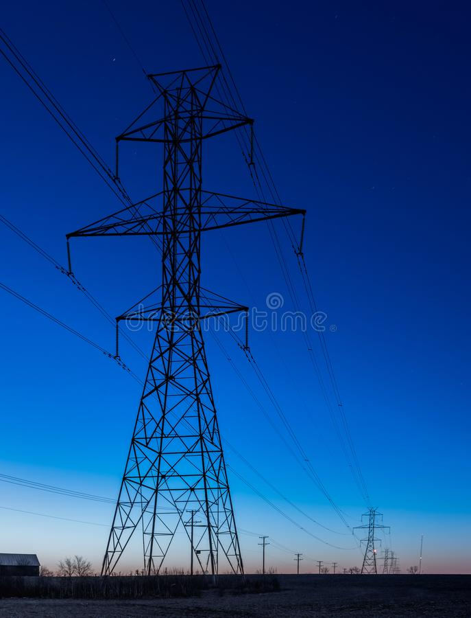 Row of power line towers during blue hour stock image