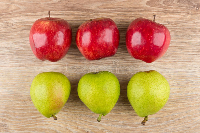 Row of red apples and green pears on wooden table royalty free stock image