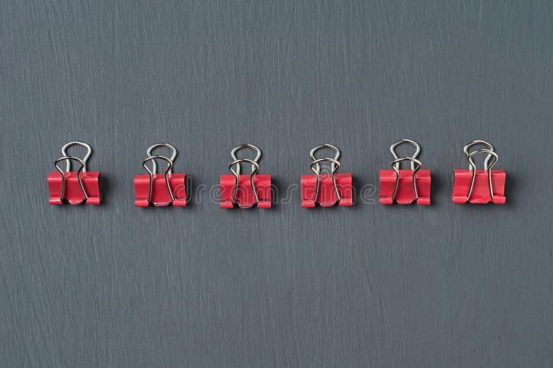 Row of red metal binders for paper on dark concrete desk in office, school or home. Close-up stock photography