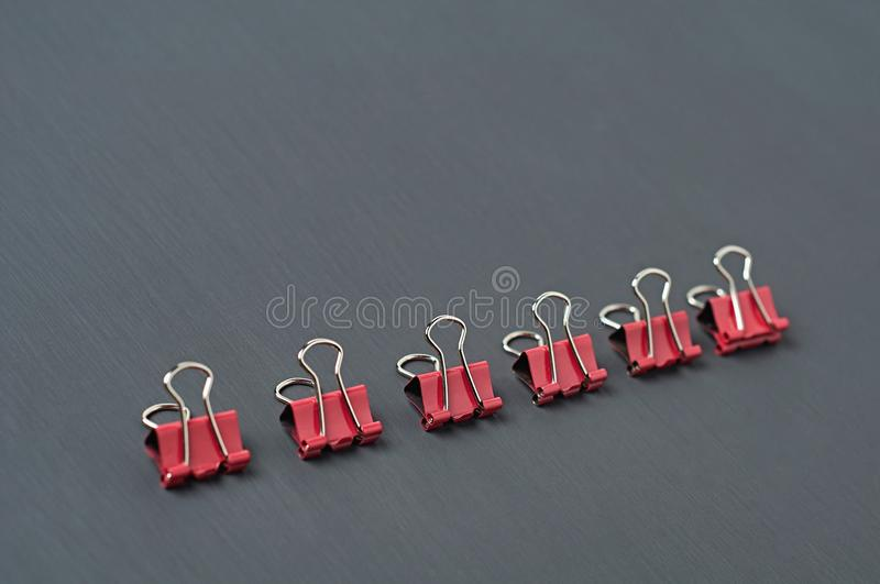 Row of red metal binders for paper on dark concrete desk in office, school or home. Space for text stock images