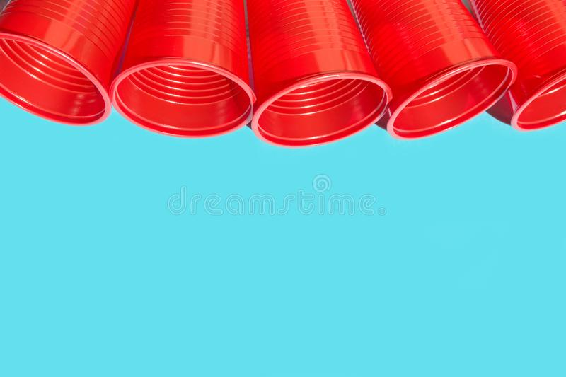 Row of red plastic drinking cup on blue background. Environmental protection plastic-free alternatives nature friendly living. Hard light harsh shadows stock photos