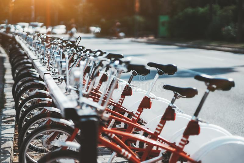 Row of red rental bikes outdoors. The row of vivid red public bicycles outdoors shot with shallow depth of field; plenty of rentable city bikes on the street on royalty free stock images