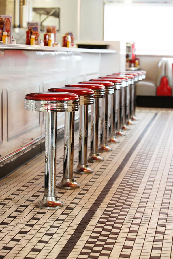 Bar stools in a fifties style diner. A row of red and silver bar stools at the counter in a fifties style diner stock photography