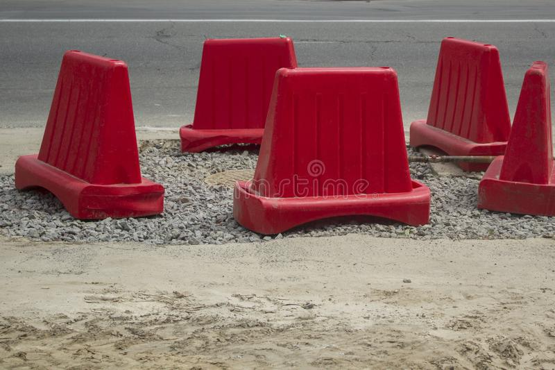 Row of red traffic cones barrier on the road under reconstruction royalty free stock photo