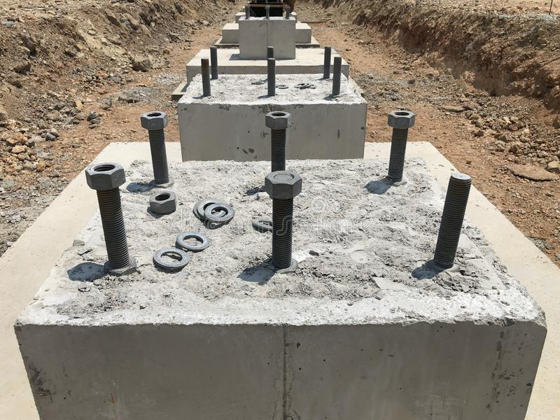 Row of reinforced concrete foundations with metal anchor bolts designed for the installation of metal columns. Foundations of warehouse on the construction stock image