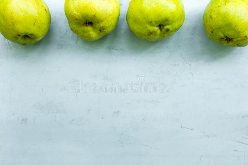 Row of ripe organic yellow green pears on scratched grey metal background. Autumn fall harvest cozy atmosphere. Local bio produce royalty free stock photos