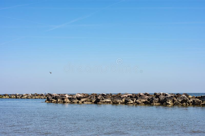 A row of rocks brought by man. A row of rocks brought by the man to defend the beach against waves and storm surges royalty free stock photo