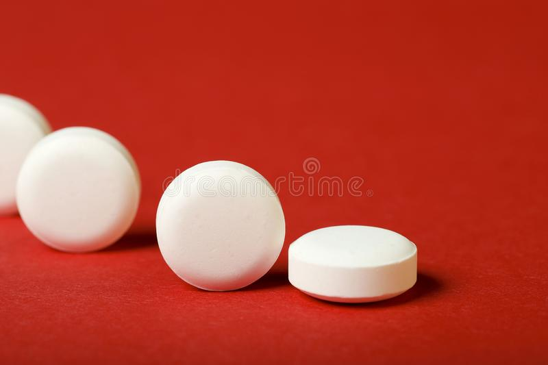 A row of round white pills on a red background. Horizontal, close-up, free space, without people, side view. The concept of medicine stock images