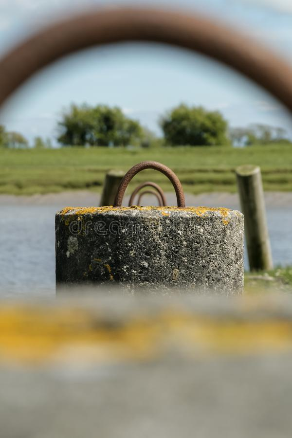 Row of mooring hoops by a lake. Row of rusty metal mooring hoops in concrete, by a lake in Scotland royalty free stock photo