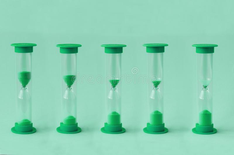 Row of sand watches with different level of falling sand inside of them.Concept of running time stock photography